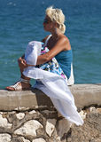 härlig blond tyckande om flicka nära havssunen Arkivbilder