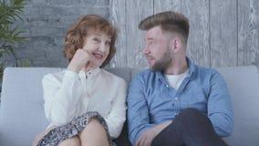 H?bsche elegante reife Frau, die mit jungem Mann im blauen Hemd zu Hause sitzt auf dem Sofaabschlu? oben spricht verh?ltnis stock video footage
