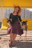 H?bsche gl?ckliche redheaded Frau mit zwei wenigen Hunden auf der gelben Sommerbank lizenzfreie stockfotos