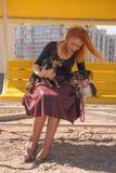 H?bsche gl?ckliche redheaded Frau mit zwei wenigen Hunden auf der gelben Sommerbank stockfoto
