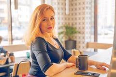 H?bsche gl?ckliche redheaded kaukasische Frau im schwarzen Hemdgetr?nktasse kaffee im modernen Caf? allein stockfotografie
