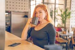 H?bsche gl?ckliche redheaded kaukasische Frau im schwarzen Hemdgetr?nktasse kaffee im modernen Caf? allein stockbild