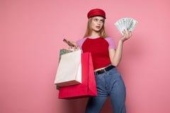 H?bsche junge Frau in der zuf?lligen Kleidung und im modischen roten Hut mit bunten Einkaufstaschen und Geld in den H?nden stockfotos