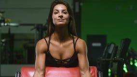 H?bsche kaukasische Eignungsfrau, die oben Muskeltrainingseignung und bodybuildende Konzeptturnhallenhintergrund-ABS?bungen in Tu stock video footage