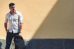 H?bscher erwachsener Mann geht entlang gelbe Wand, Kopienraum stockbild