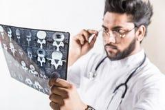 H?bscher junger Doktor in einem wei?en Mantel mit einem Stethoskop ?berpr?ft aufmerksam den R?ntgenstrahl des Patienten lizenzfreies stockfoto