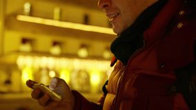H?bscher junger Mann in der roten Jacke passt Fotos auf seinem Smartphone am Abend auf stock video