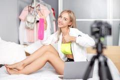 H?bscher junges M?dchen Blogger, der in der modernen Kleidung gekleidet wird, wird f?r die Werbung des Sitzens auf dem Bett mit g lizenzfreies stockfoto