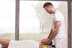H?bscher l?chelnder Masseur, der Massage tut stockbilder