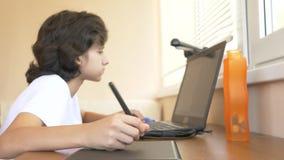 H?bscher moderner Jungenjugendlicher, der an einer grafischen Tablette arbeitet Er betrachtet den Laptopschirm 4k, Zeitlupe stock footage