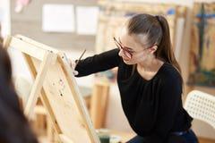 H?bsches blondes M?dchen in den Gl?sern, die in der schwarzen Bluse gekleidet werden, sitzt am Gestell und malt ein Bild im Kunst stockbild