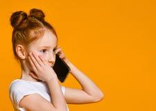 H?bsches emotionales kleines M?dchen, das durch Handy spricht stockfotos
