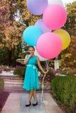 H?bsches junges M?dchen mit gro?en bunten Ballonen gehend in den Park nahe der Stadt - Bild stockfoto