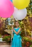 H?bsches junges M?dchen mit gro?en bunten Ballonen gehend in den Park nahe der Stadt - Bild lizenzfreie stockfotografie