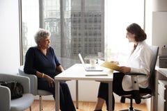 H?g kvinna som har konsultation med kvinnlig doktor In Hospital Office fotografering för bildbyråer