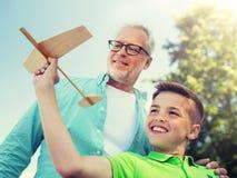 H?g man och pojke med leksakflygplanet ?ver himmel royaltyfri foto