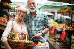 H?ga familjpar som v?ljer den bio matfrukt och gr?nsaken p? marknaden under veckoshopping arkivfoto