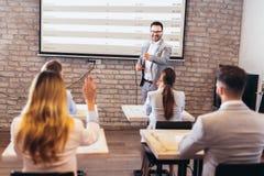 H?gtalare som ger offentlig presentation genom att anv?nda projektorn i konferensrum royaltyfri bild