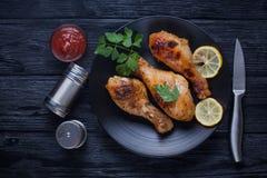 H?hnerbeine mit Tomaten, Zitrone, Petersilie und Ketschup auf einem Schwarzblech lizenzfreies stockfoto