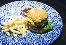 H?hnerhamburger, -fischrogen und -so?e auf der blauen Platte im Restaurant lizenzfreie stockfotografie