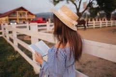 H?ll f?r elegant kvinna en bok och en bukett av blomman i hand Hon st?r i f?ltet Bakgrund av lantg?rden L?sning boka royaltyfri foto