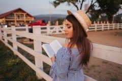H?ll f?r elegant kvinna en bok och en bukett av blomman i hand Hon st?r i f?ltet Bakgrund av lantg?rden L?sning boka fotografering för bildbyråer