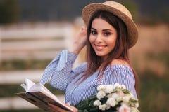 H?ll f?r elegant kvinna en bok och en bukett av blomman i hand Hon st?r i f?ltet Bakgrund av lantg?rden L?sning boka royaltyfria bilder