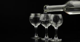 H?lla upp skott av vodka fr?n en flaska in i exponeringsglas mot svart bakgrund arkivfoto