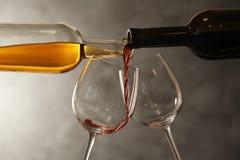 H?llande olika viner fr?n flaskor in i exponeringsglas royaltyfria bilder