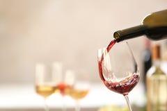 H?llande r?tt vin fr?n flaskan in i exponeringsglas p? suddig bakgrund royaltyfri bild
