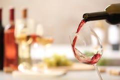 H?llande r?tt vin fr?n flaskan in i exponeringsglas p? suddig bakgrund fotografering för bildbyråer