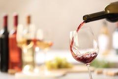 H?llande r?tt vin fr?n flaskan in i exponeringsglas p? suddig bakgrund royaltyfria bilder