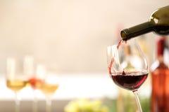 H?llande r?tt vin fr?n flaskan in i exponeringsglas p? suddig bakgrund arkivfoton