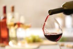 H?llande r?tt vin fr?n flaskan in i exponeringsglas p? suddig bakgrund royaltyfria foton