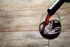 H?llande r?tt vin fr?n flaskan in i exponeringsglas p? tr?bakgrund royaltyfria foton