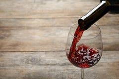 H?llande r?tt vin fr?n flaskan in i exponeringsglas p? tr?bakgrund fotografering för bildbyråer