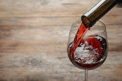 H?llande r?tt vin fr?n flaskan in i exponeringsglas p? tr?bakgrund arkivbild