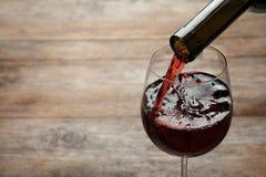 H?llande r?tt vin fr?n flaskan in i exponeringsglas p? tr?bakgrund royaltyfria bilder