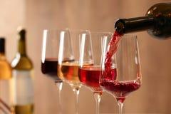 H?llande vin fr?n flaskan in i exponeringsglas p? suddig bakgrund royaltyfri fotografi