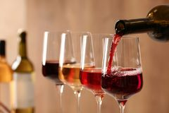 H?llande vin fr?n flaskan in i exponeringsglas p? suddig bakgrund royaltyfri bild