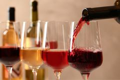 H?llande vin fr?n flaskan in i exponeringsglas p? suddig bakgrund arkivbild