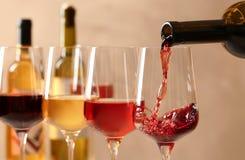 H?llande vin fr?n flaskan in i exponeringsglas p? suddig bakgrund royaltyfria bilder