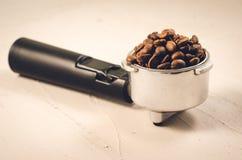 h?llare som fylls med kaffeb?nor/h?llare som fylls med kaffeb?nor p? en konkret bakgrund arkivbilder