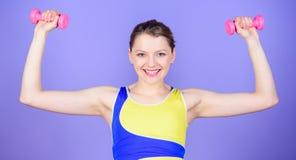 H?lsa bantar framg?ng Starka muskler och makt Lycklig kvinnagenomk?rare med skivst?ngen Sporthantelutrustning athirst royaltyfria bilder