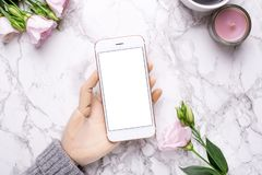 H?lzerne Hand mit Handy auf Marmorb?rohintergrund mit rosa Blumen stockbild