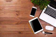 H?lzerne Schreibtischtabelle mit Laptop, Tasse Kaffee und Versorgungen stockfoto