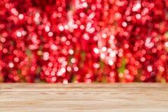 H?lzerne Tischplatte auf rotem bokeh Zusammenfassungshintergrund lizenzfreie stockfotos