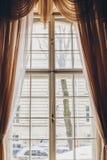 H?lzernes Fenster mit Weinlesevorh?ngen und quadratisches Formteil an einem sonnigen Tag beige Satinvorh?nge innen Hintergrund f? stockbild