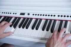 H?nde, die das wei?e Klavier spielen lizenzfreie stockfotografie