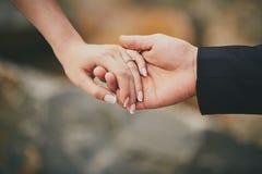 H?nde eines jungen Paares mit einem Ring Schlie?en Sie oben vom Mann, der der Frau Diamantring gibt lizenzfreie stockfotos